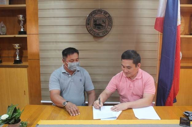 Mayor Demetrius Narag signs the MOU, sealing the partnership between Basco and Coca-Cola Beverages Philippines for PET plastic bottle collection and recycling . Mayor Narag is joined by Mr. Carlito Cari, Municipal Environment Officer of Basco.